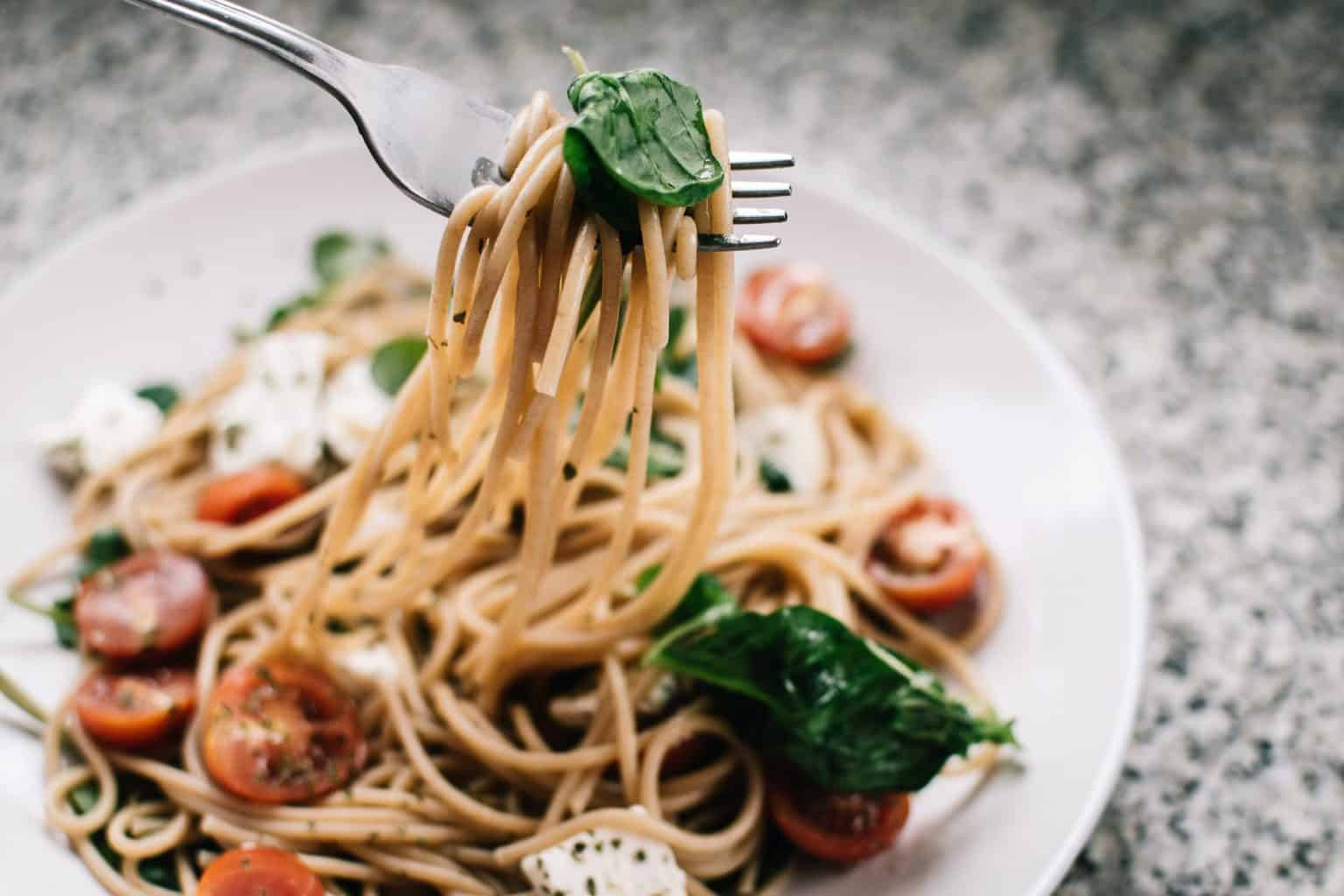 selective focus photography of pasta with tomato and basil 1279330 scaled - Contact